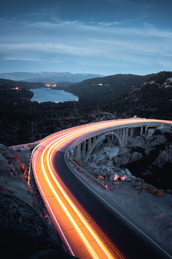 High angle view of light trails on road against sky at dusk