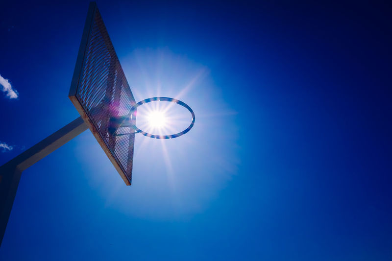 Low angle view of illuminated lamp against blue sky