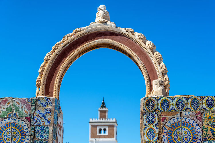 Old historic colorful arch with a mosque in the background in Tunis, Tunisia City Downtown Medina Mediterranean  Rooftop Travel Tunis Tunisia Africa Arabic Arch Architecture Building Built Structure Capital Culture Historic House Landmark Mosque Ornate Outdoors Street Tourism Traditional