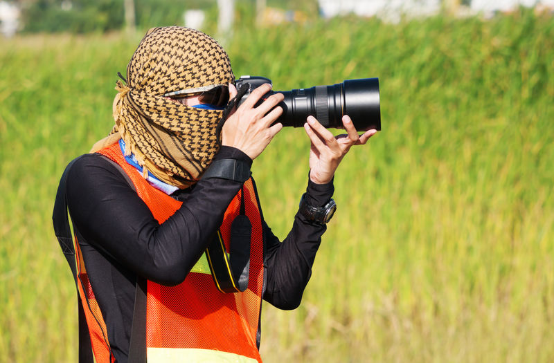 Camera - Photographic Equipment Camera Operator Day Digital Single-lens Reflex Camera Grass Hat Looking Through An Object Mid Adult Movie Camera Nature One Person Outdoors Paparazzi Photographer People Photographer Photographing Photography Themes Protection Real People Safety SLR Camera Technology
