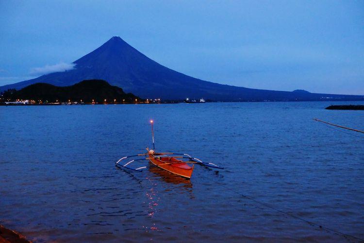 Scenic view of calm sea against mountain range