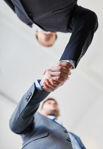 Low angle view of business people shaking hands in office