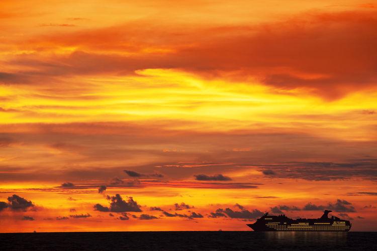 Silhouette cruise ship sailing on sea against cloudy sky at sunrise