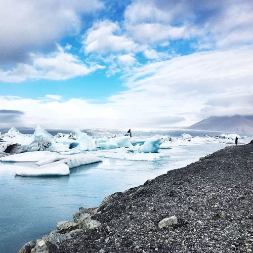 Scenic view of glacier lagoon against cloudy sky
