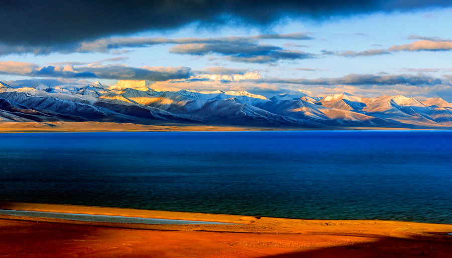 Snow covered mountain and Nam lake at sunrise, Tibet, China Beauty In Nature Clear Cloud - Sky Colorful Lake Landscape Mount Mountain Mountain Peak Mountain Range Nature No People Outdoors Peaceful Reflection Scenics Snow Sunlight Sunrise Tibet Tourism Tranquility Travel Travel Destinations Water