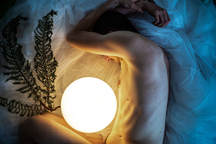 Low section of man with lamp lying on bed