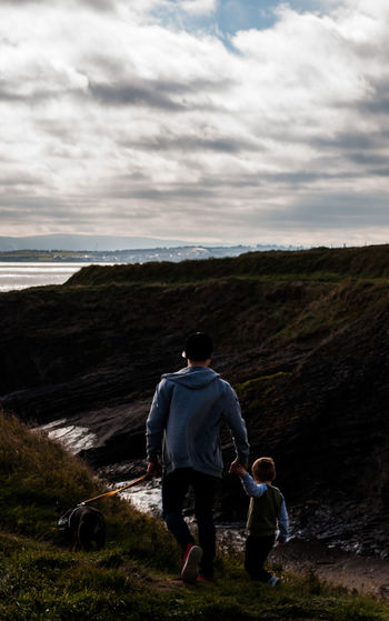 Rear View Of Father And Son Walking On Mountain Against Cloudy Sky During Sunset