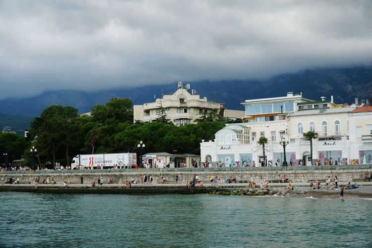 View of town at waterfront against cloudy sky