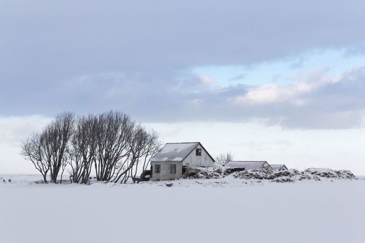 House on snow covered field against sky