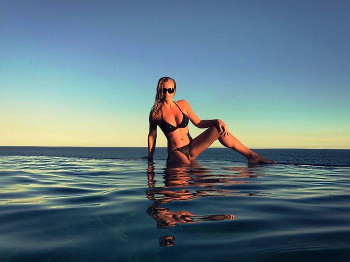 Young woman in bikini sitting on edge of infinity pool against clear sky