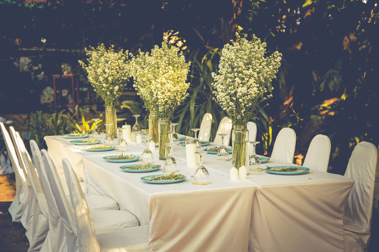 Empty chairs and tables arranged against plants at wedding ceremony