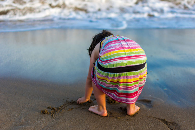 Sand One Person Water Beach Land Real People Full Length Nature Leisure Activity Day Sand Women Child Childhood Lifestyles Sea Focus On Foreground Outdoors Seashore Game Playing Play