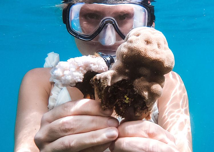 Portrait of woman holding coral in sea
