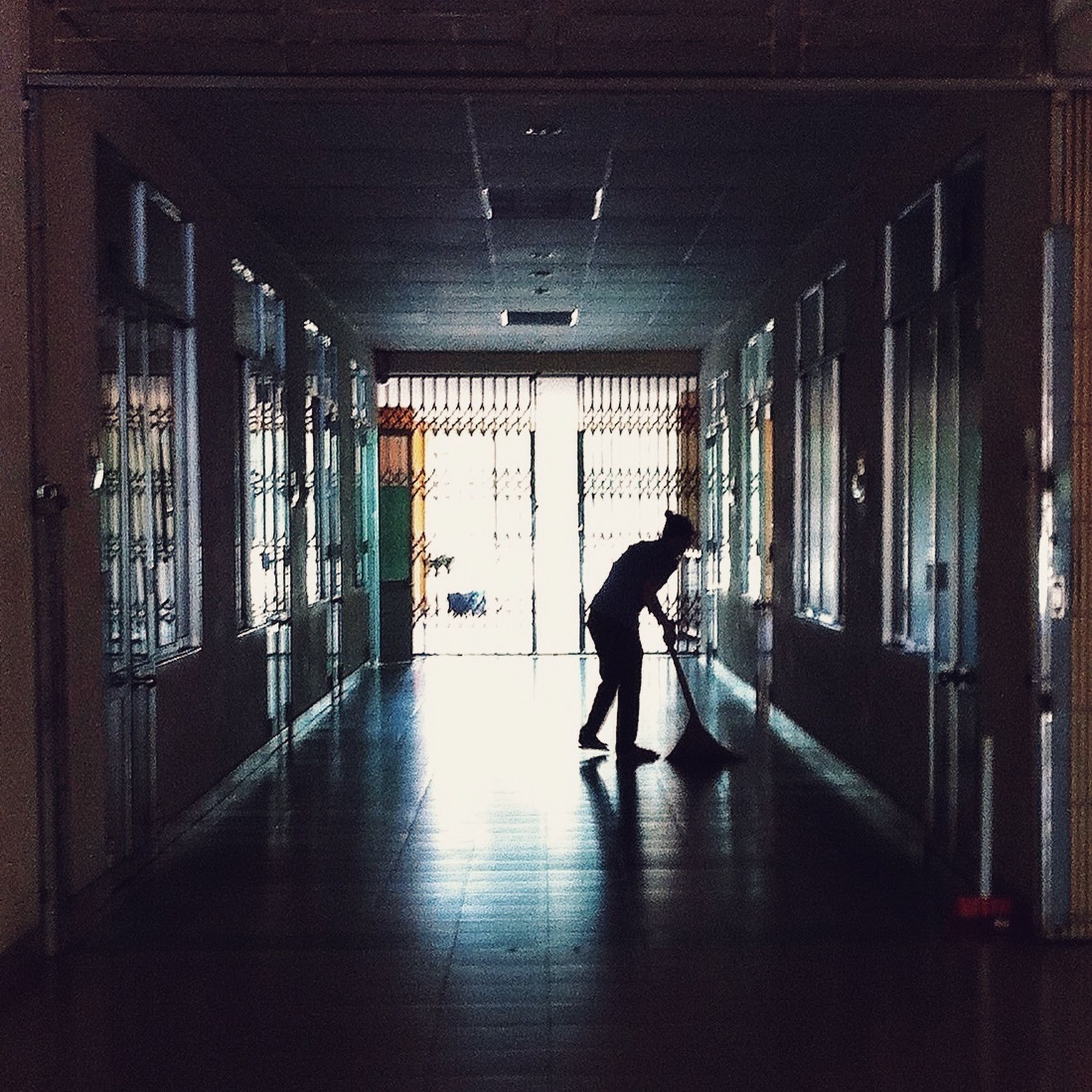 indoors, full length, architecture, lifestyles, built structure, walking, men, leisure activity, corridor, window, rear view, reflection, building, person, flooring, wall - building feature, silhouette, illuminated