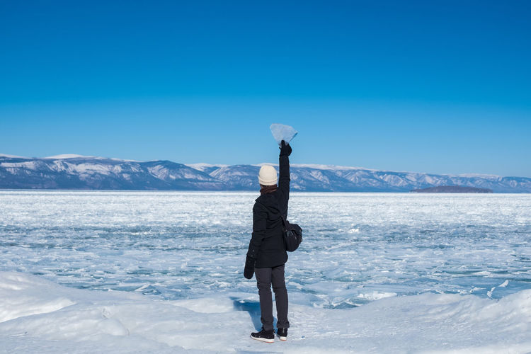 Woman standing on snowcapped mountain against blue sky