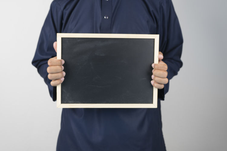 Midsection of man holding slate against gray background