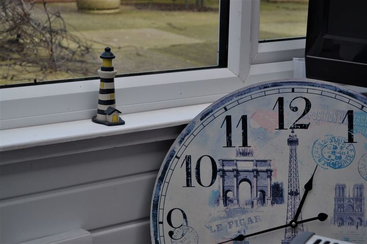 Blue and white striped wooden lighthouse ornament and a Paris theme large clock by the window - random placement of odd things. No People Window Day Glass - Material Text Transparent Communication Close-up Number Outdoors Focus On Foreground Clock Built Structure Architecture Time Wall - Building Feature Nature Graffiti Random Wooden Lighthouse Paris Paris Theme