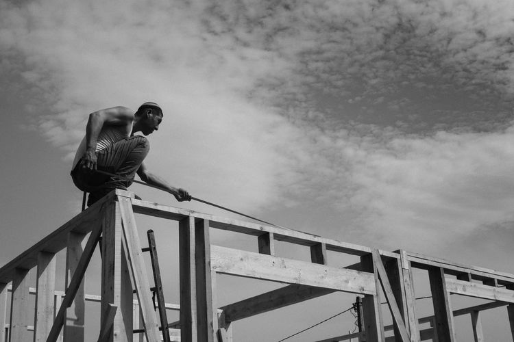 Low angle view of construction worker against sky
