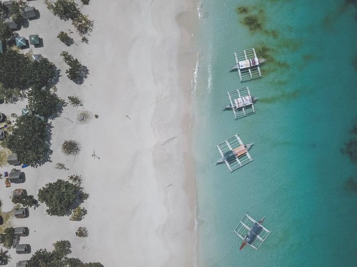 Directly above shot of outrigger canoes on shore at beach
