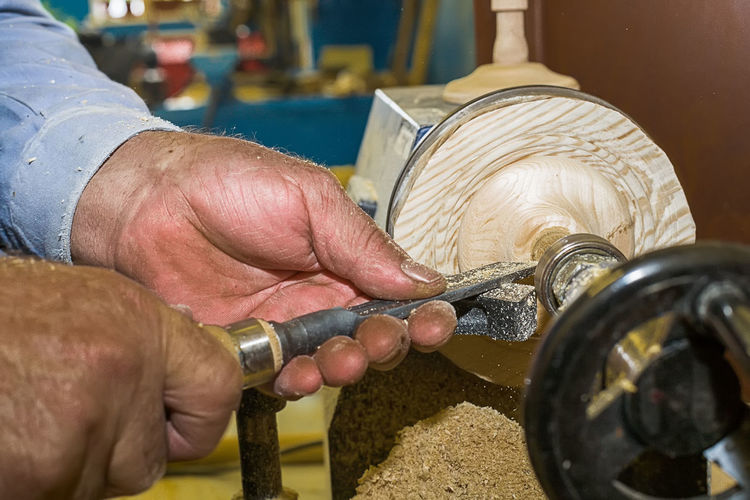Cropped hands of carpenter holding work tool