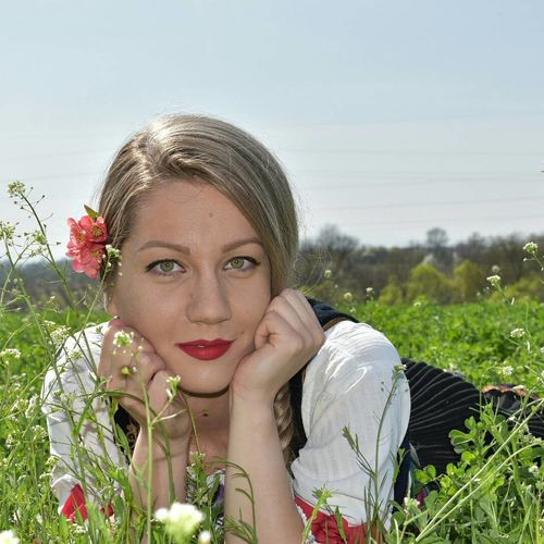 Portrait of young woman wearing flowers while lying on grassy field
