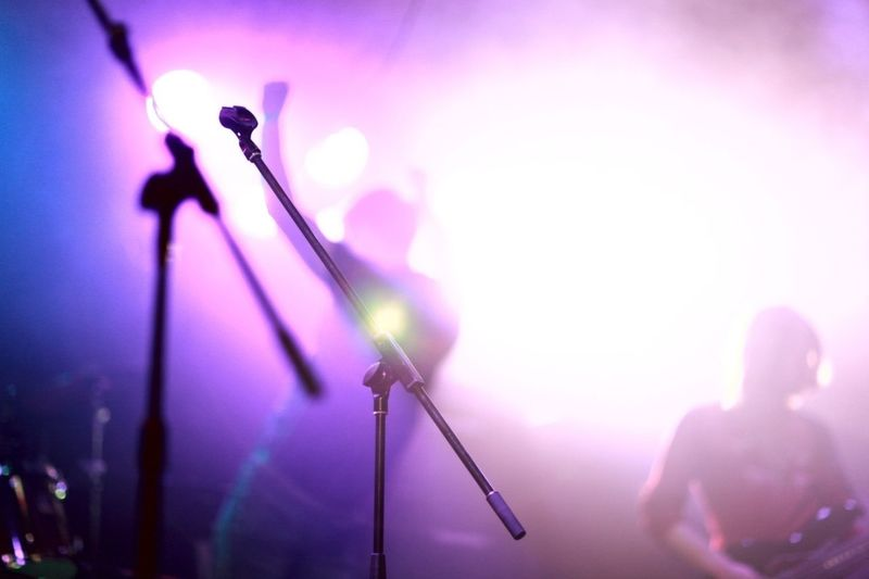 Microphone in front of musicians performing in music concert