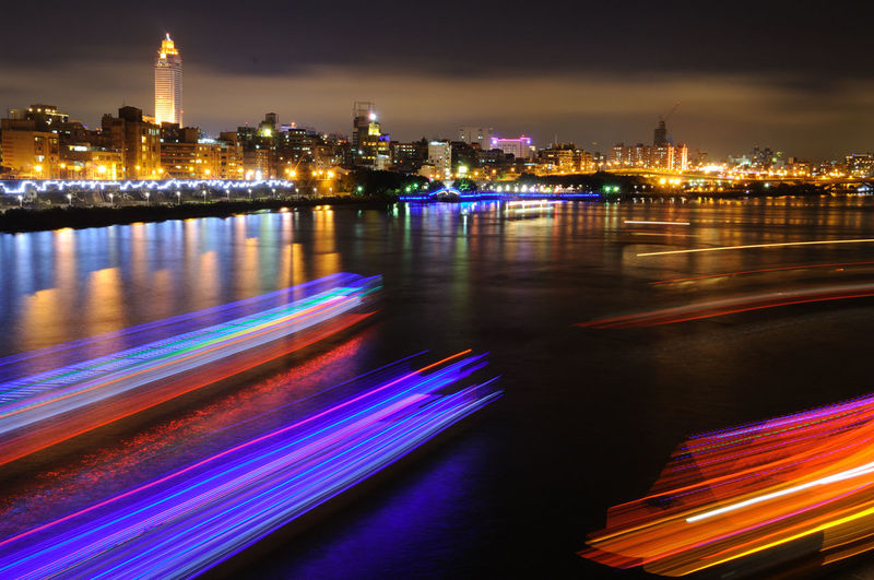 Light trails on river by illuminated buildings in city at night