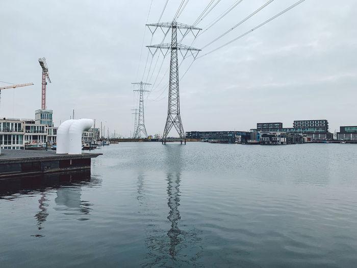 Bridge over factory against sky