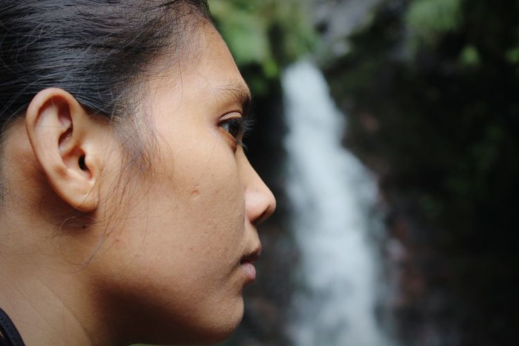 Close-up portrait of woman in front of waterfall
