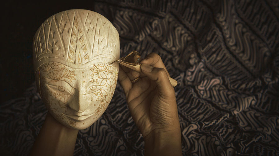 Cropped hand of woman carving mask