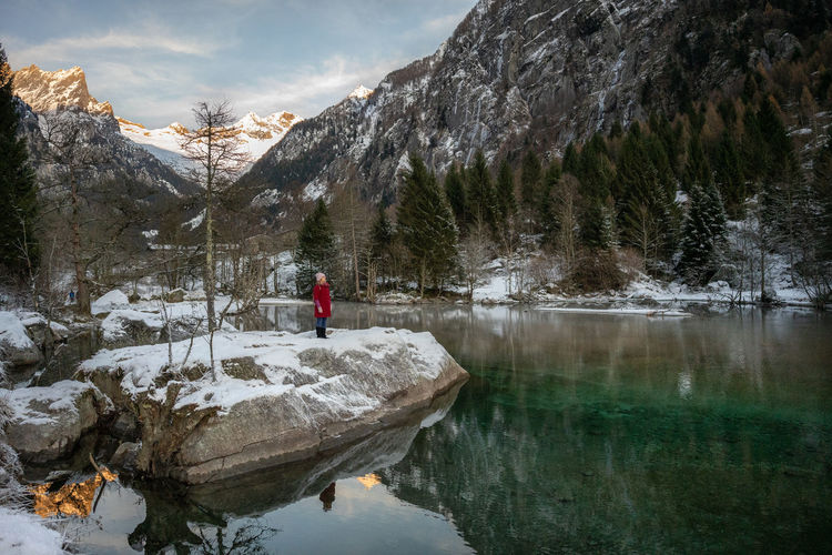 Man on rock by lake against mountain during winter