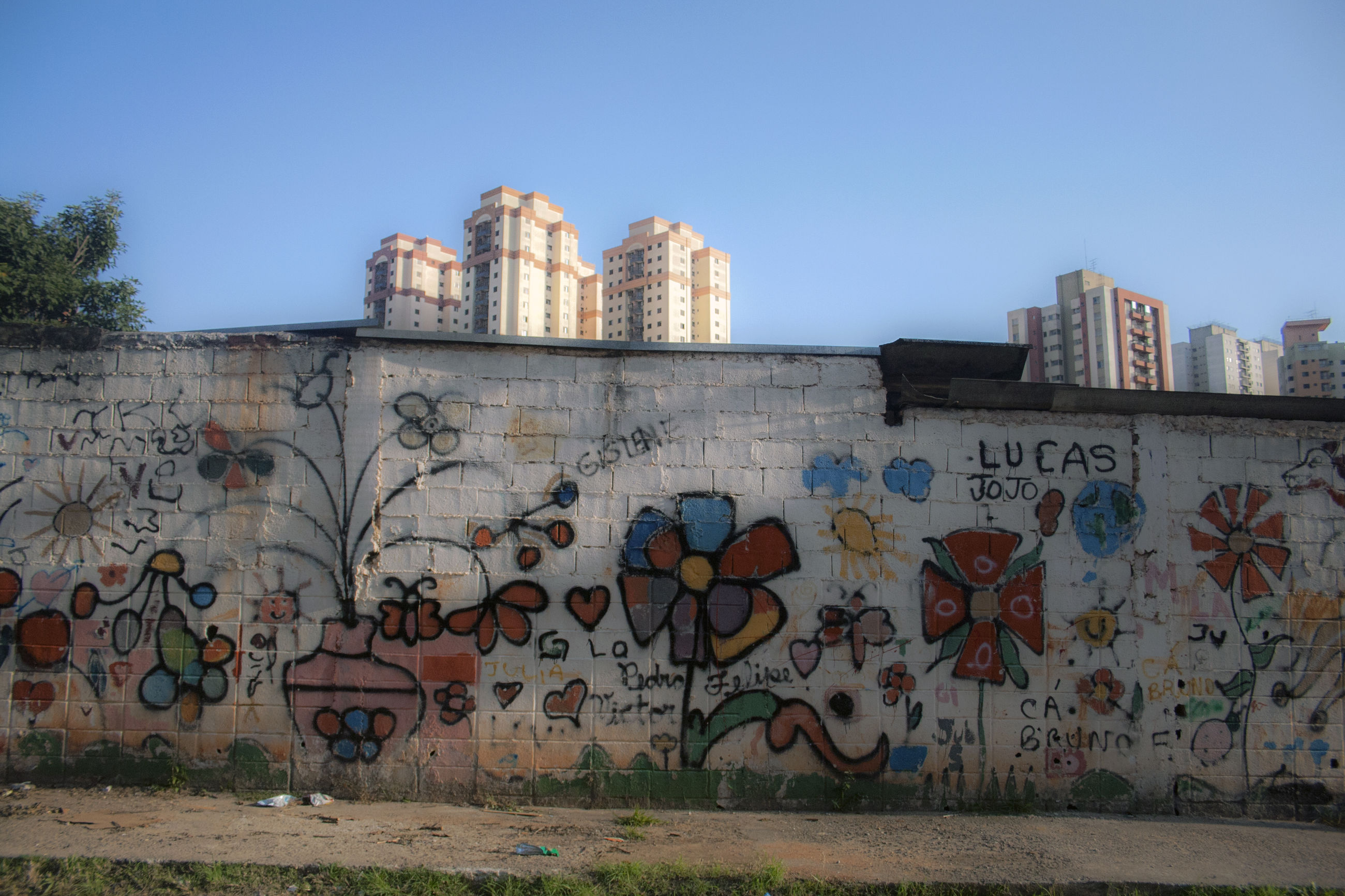 architecture, built structure, building exterior, graffiti, clear sky, wall - building feature, art, creativity, art and craft, blue, text, western script, building, day, outdoors, city, copy space, no people, wall, sky