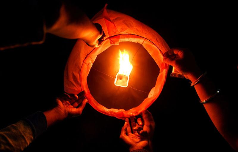 Cropped Hands Holding Illuminated Paper Lantern