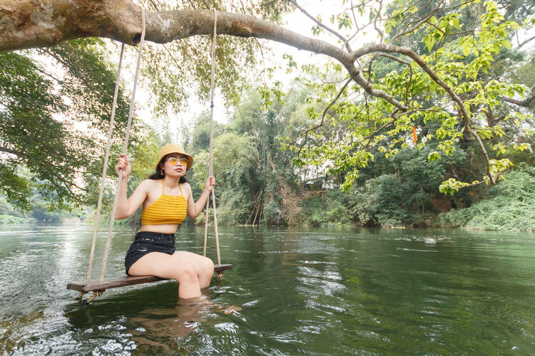 Young woman sitting on rope swing in river at forest