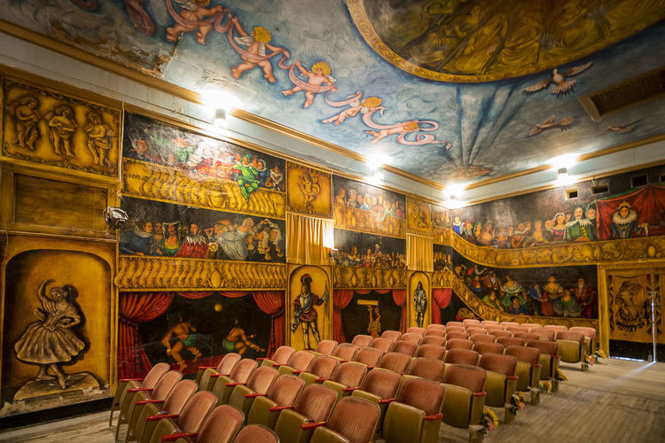 Old opera house Absence Architecture Art And Craft Arts Culture And Entertainment Belief Built Structure Ceiling Empty Fresco Human Representation Illuminated In A Row Indoors  Large Group Of Objects Lighting Equipment Mural No People Ornate Place Of Worship Religion Representation Seat Stage