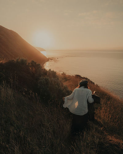 Rear view of man looking at sunset
