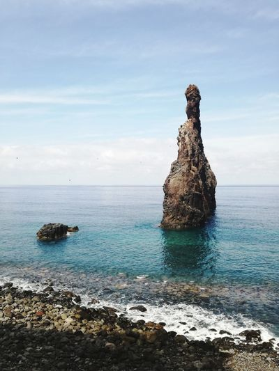 Rock formation on sea against sky