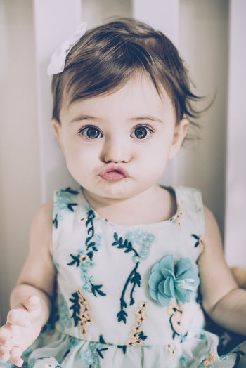 Portrait Of Cute Baby Girl Puckering Lips While Sitting At Home