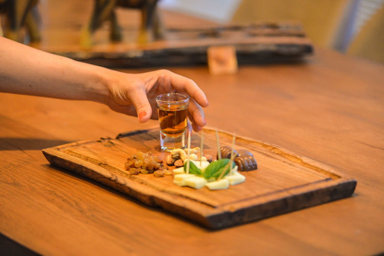 Alcohol Chopping Chopping Board Close-up Cutting Board Day Drink Food Food And Drink Freshness Healthy Eating Holding Human Body Part Human Hand Indoors  Lifestyles One Person People Preparation  Real People Refreshment Selective Focus Table Vegetable Wood - Material