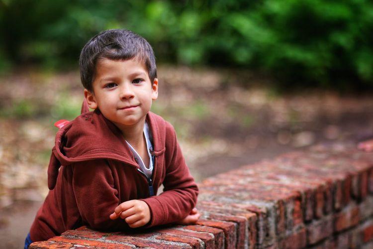 Little boy posing in a brick wall
