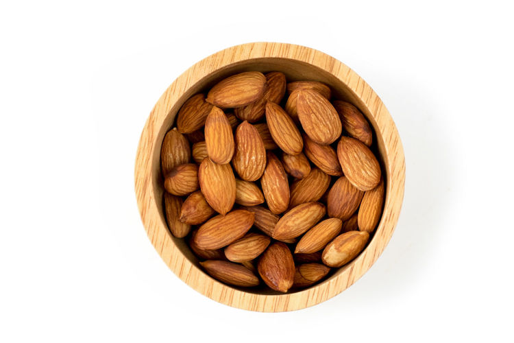 Close up of almonds nut seeds isolated in wooden bowl against top view on white background and clipping path. Almonds Isolated White Background Food And Drink Healthy Eating Brown Organic Snack Heap Freshness Plant Object Group Nutrition Seed Fruit Nuts Diet Delicious Tasty Ingredient Vegetarian Clipping Path Wooden Bowl