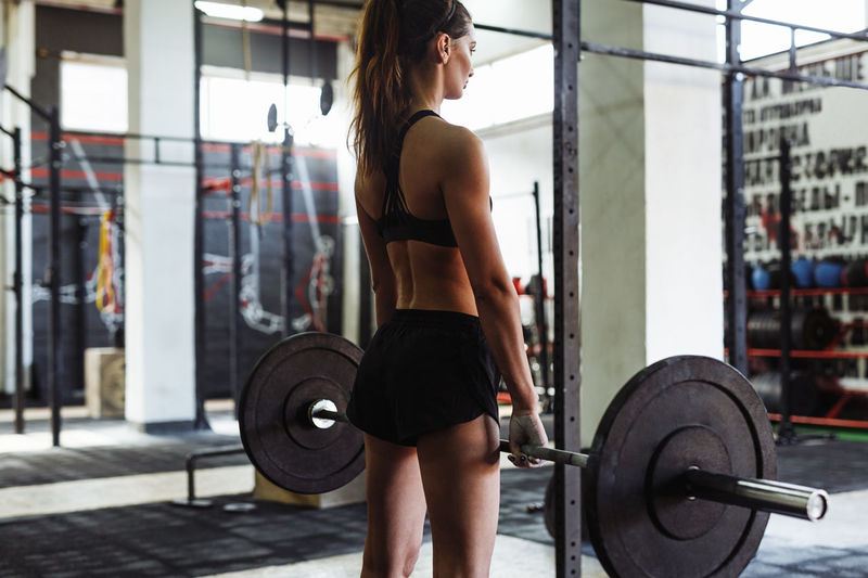 Young Woman Lifting Barbell At Gym