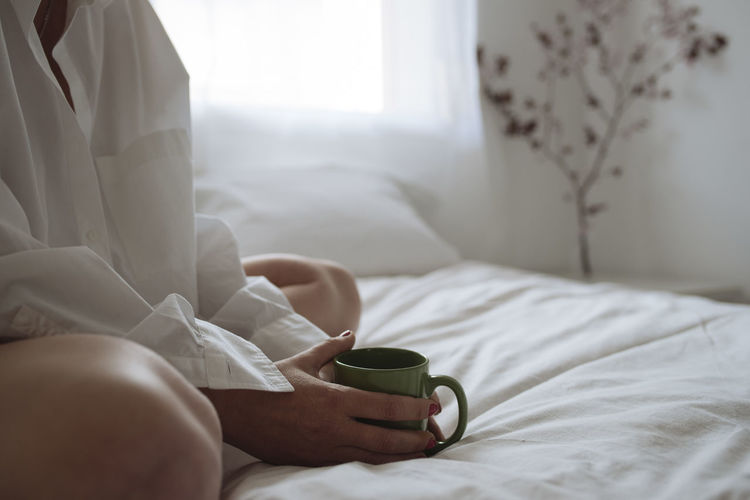 Midsection of woman holding coffee cup on bed at home