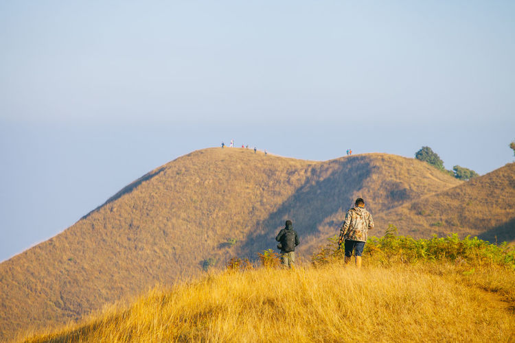 Rear View Of Male Hikers On Field Against Mountain