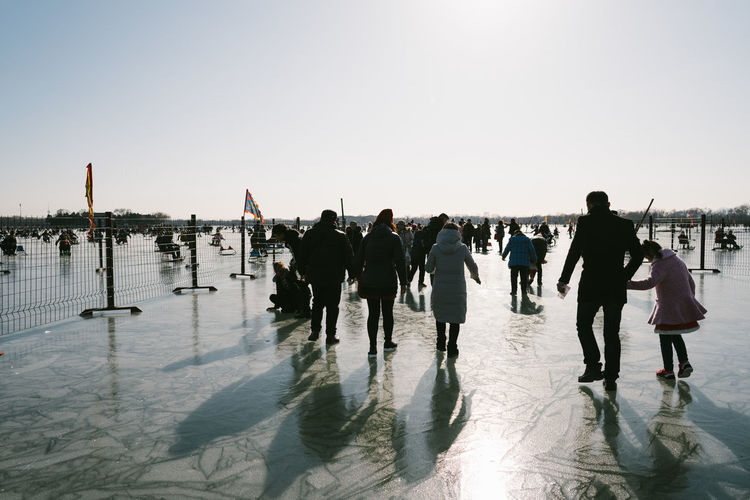 Rear view of people walking on frozen lake