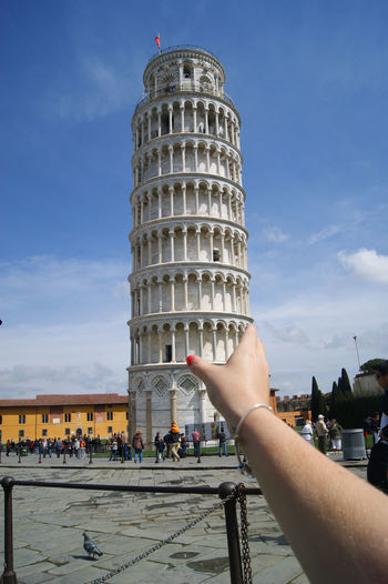 Optical illusion of woman holding leaning tower of pisa