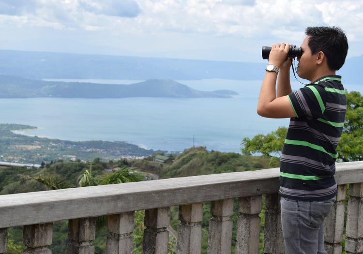 Man looking through binoculars while standing by sea against sky