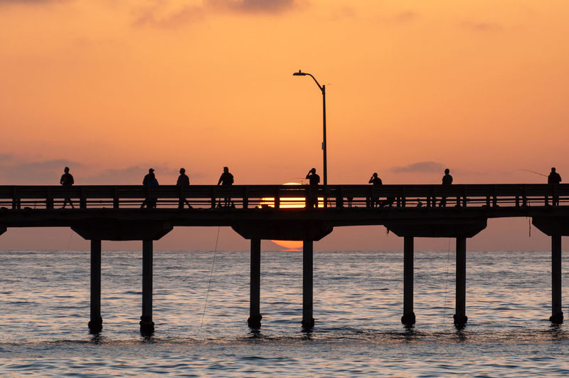 Silhouette people on pier over sea against sky during sunset