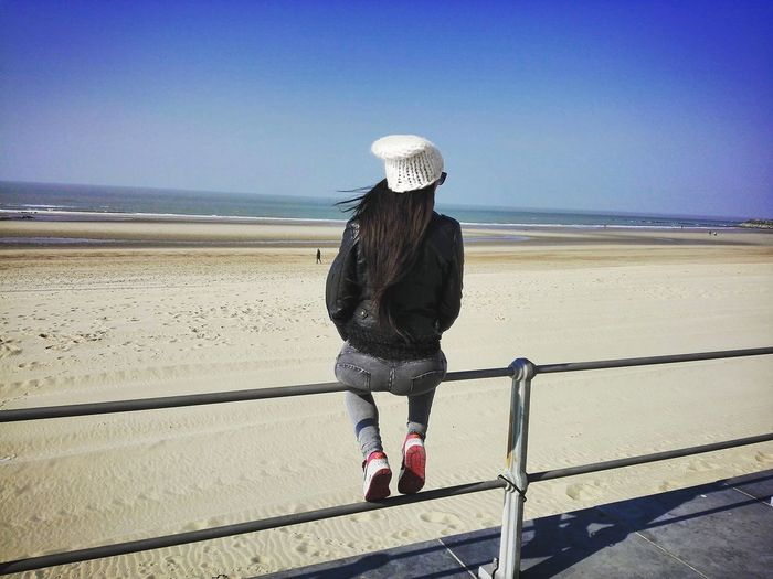 Rear view of woman sitting on railing at beach against clear sky