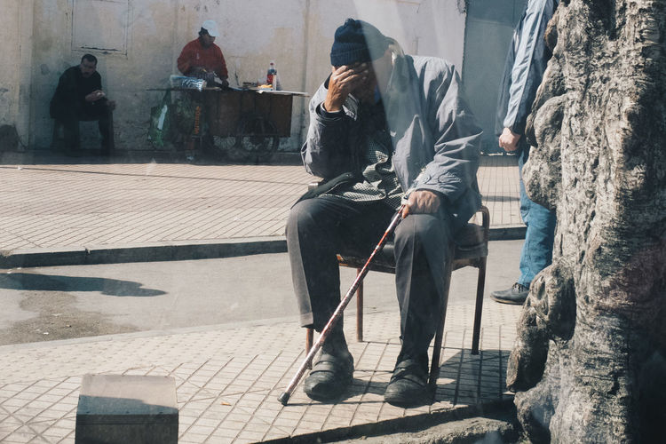 Full length of man with head in hand sitting on street